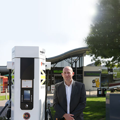 John Lowes next to a rapid charge network point